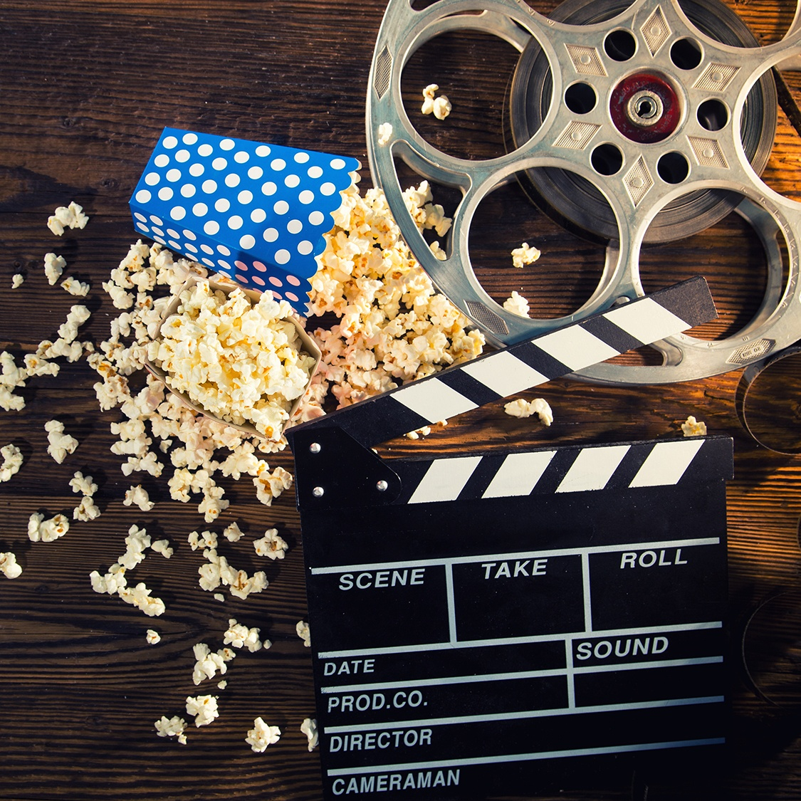 Cinema,Concept,Of,Vintage,Film,Reel,With,Popcorn,On,Old